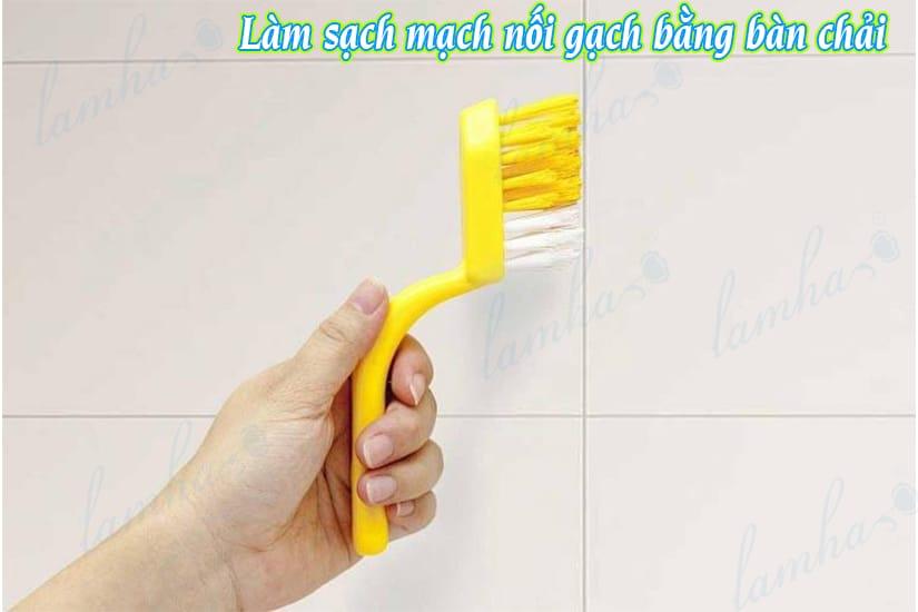Làm sạch mạch nối gạch nhà vệ sinh bằng bàn chải